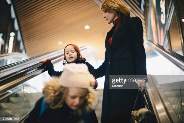 Mother and daughters moving down on escalator at railroad station
