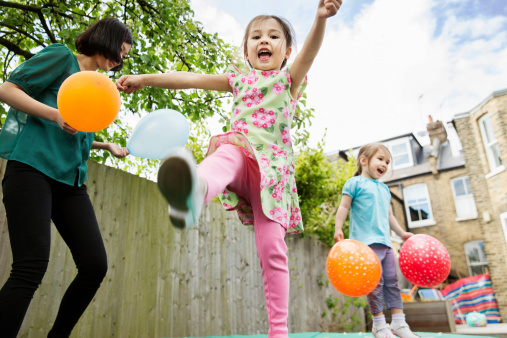 Mother and daughters playing in garden with balloons - gettyimageskorea