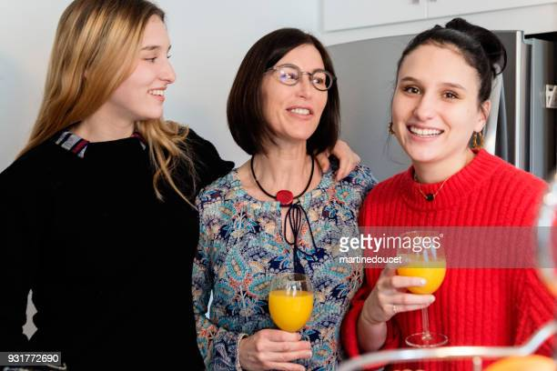 mother and daughters portrait having a drink at family reunion. - mimosa stock pictures, royalty-free photos & images