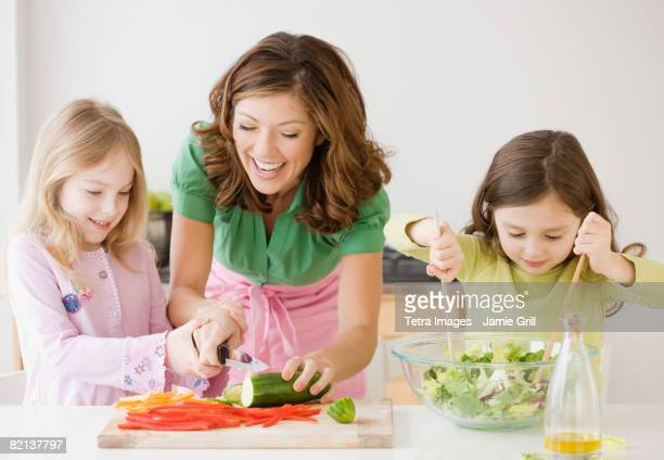 Mother and daughters preparing food