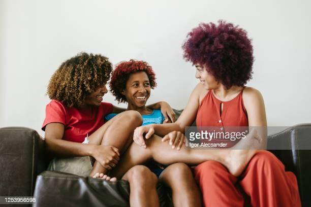 母と娘はソファでリラックス - コイリーヘア ストックフォトと画像