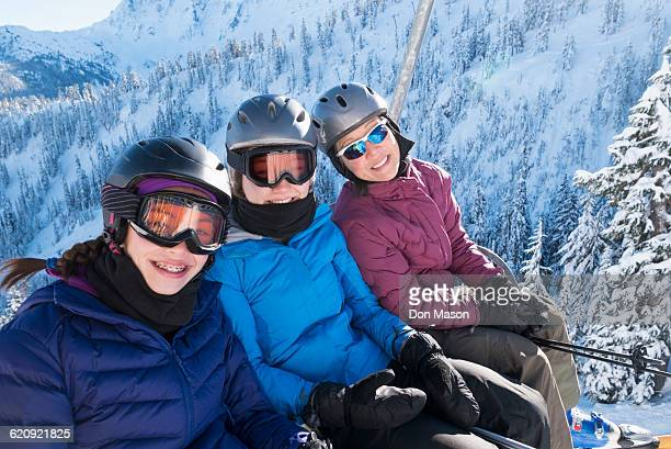 Mother and daughters riding ski lift