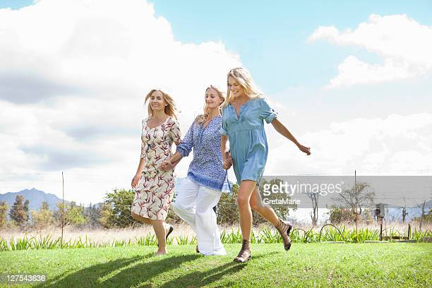 mother and daughters running in garden - skipping along stock pictures, royalty-free photos & images