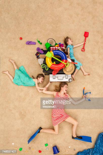 Mother and daughters running to the sea, carrying beach equipment on the head