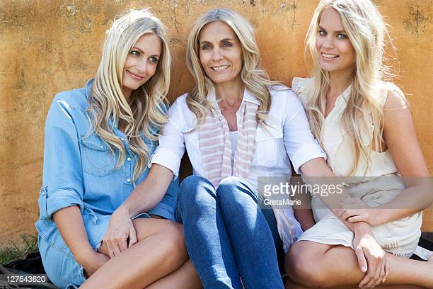 mother and daughters sitting together - two generation family stock pictures, royalty-free photos & images