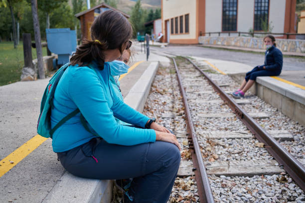Mother and daughters sitting train station before railroad tracks