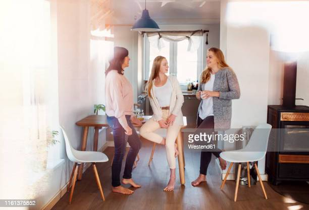mother and daughters standing in kitchen, talking, drinking coffee - scalzo foto e immagini stock