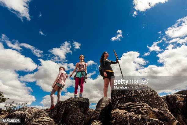 Mother and daughters standing on top of cliff