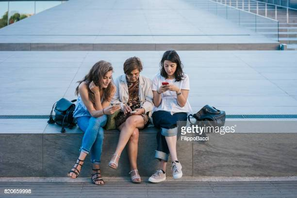 Mother and daughters surfing the net with smartphone