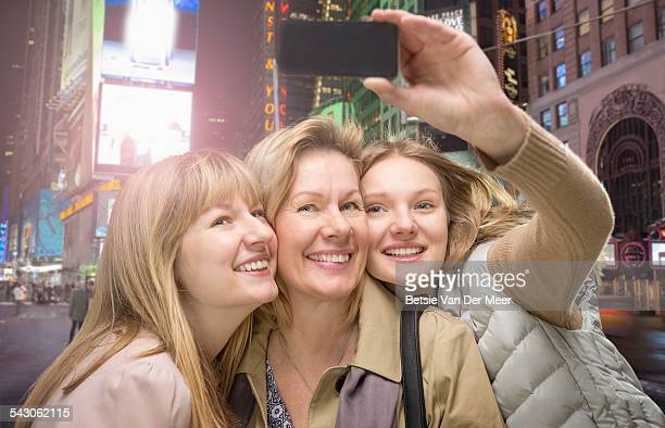 Mother and daughters take Selfie in city at nighth