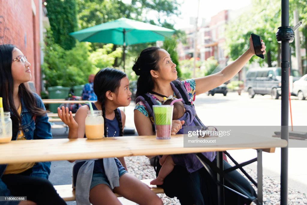 Mother and daughters taking a selfie outdoors on store terrace. : Stock Photo