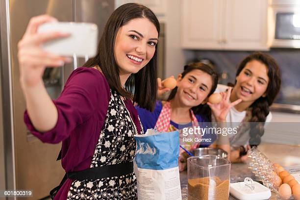 Mother and daughters taking selfie in kitchen