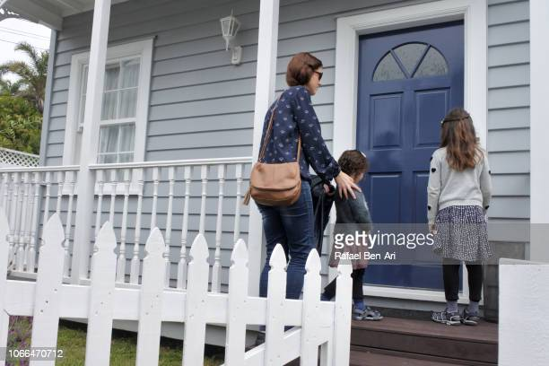 Mother and Daughters Waiting Outside a Home Front Door