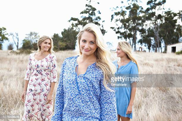 Mother and daughters walking in field