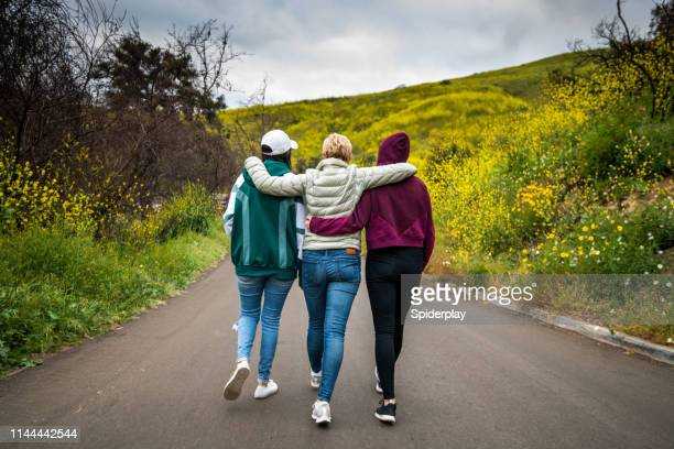 mother and daughters walking towards the flower field - arm in arm stock pictures, royalty-free photos & images