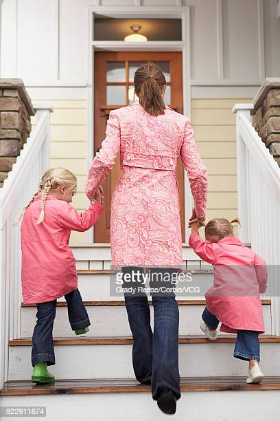 Mother and daughters walking up steps