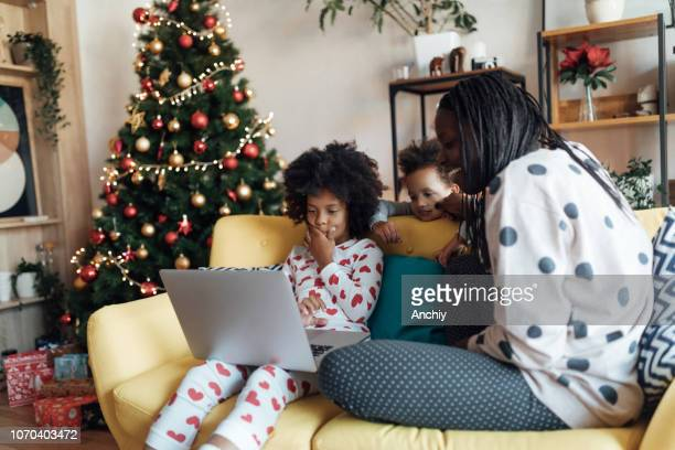 Mother and daughters watching cartoons on laptop