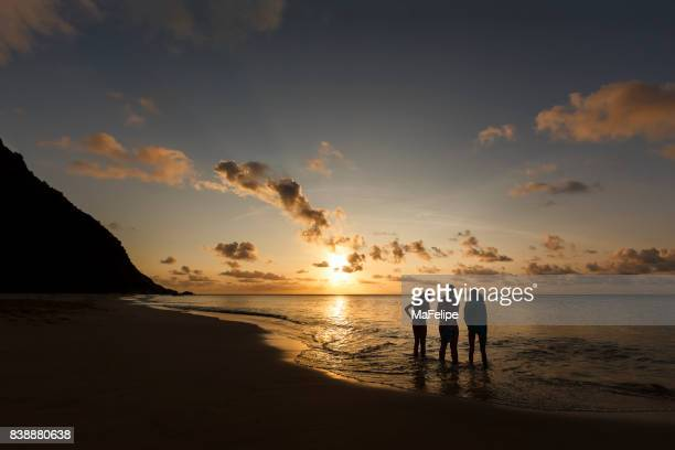 Mother and daughters watching sunset in Fernando de Noronha