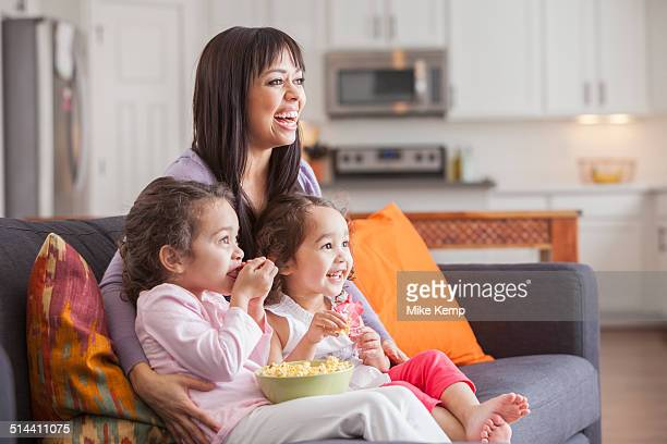 Mother and daughters watching television on sofa