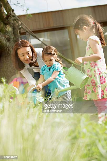 Mother and daughters watering garden