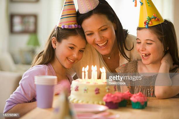 Mother and daughters with birthday cake