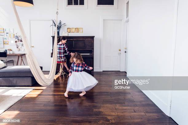 mother and daugther enjoying the tunes of an upright piano at their loft apartment - flooring stock photos and pictures