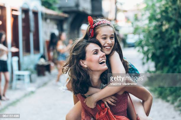 mother and daugther having fun outdoors - piggyback stock pictures, royalty-free photos & images