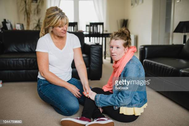 mother and disabled daughter relaxing at home - epilepsy stock pictures, royalty-free photos & images