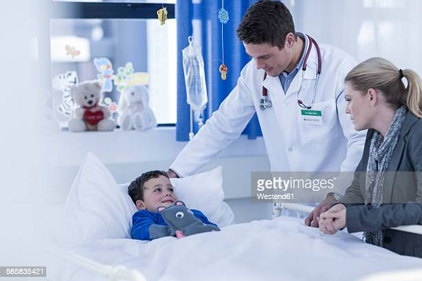 Mother and doctor visiting little boy lying in hospital bed
