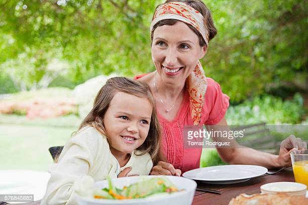mother and doughter (6-7 years) in garden, smiling - 25 29 years stock pictures, royalty-free photos & images