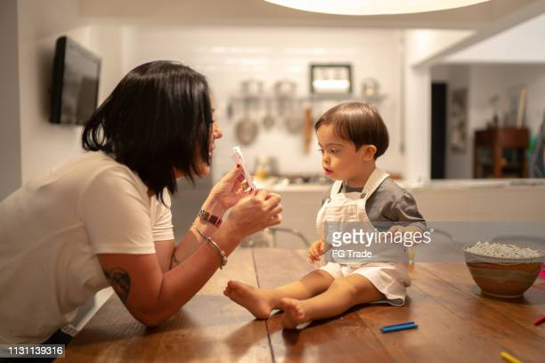 Mother and Down Syndrome son drawing and eating popcorn at table