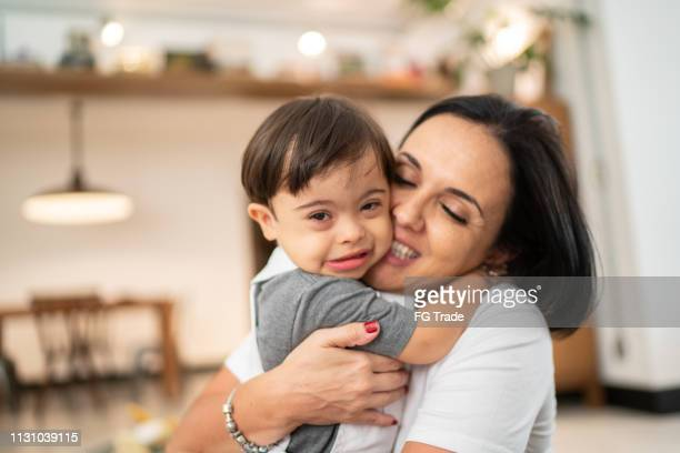 Mother and Down Syndrome Son embracing at home