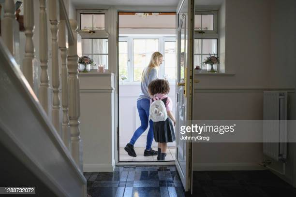 mother and elementary age daughter leaving for school - leaving stock pictures, royalty-free photos & images