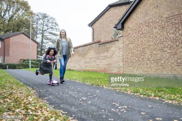 mother and energetic young girl riding scooter to school - building exterior stock pictures, royalty-free photos & images