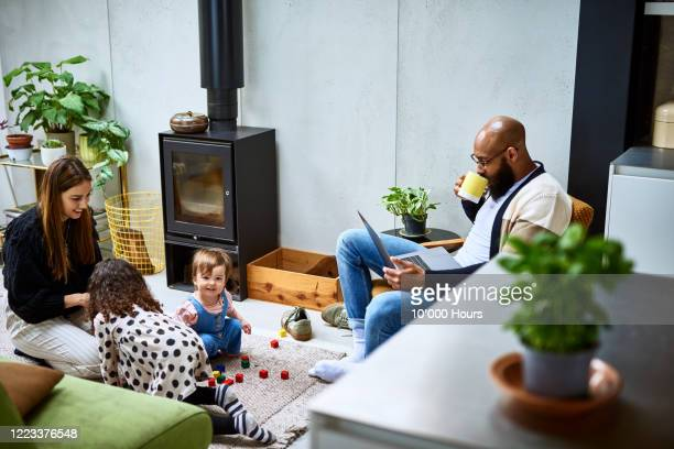 mother and father at home wit h two daughters - using laptop stock pictures, royalty-free photos & images