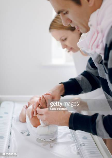 mother and father dressing newborn baby - cobham surrey stock pictures, royalty-free photos & images