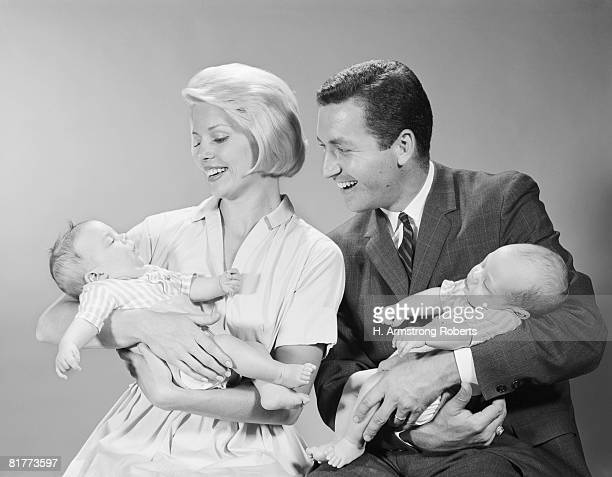 mother and father holding babies. - arrival photos stock photos and pictures