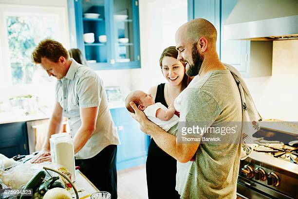 Mother and father holding newborn baby in kitchen