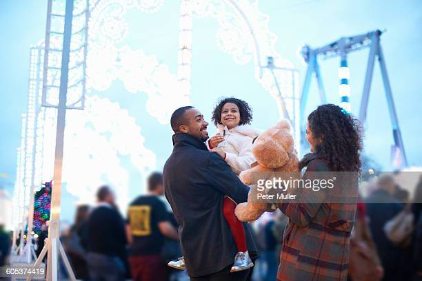 Mother and father in amusement park carrying smiling girl and teddy bear