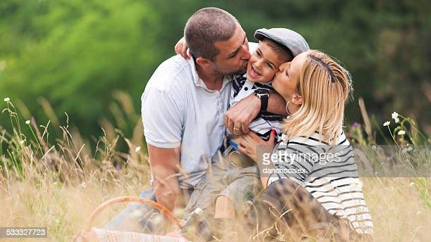 Mother and father kissing their boy