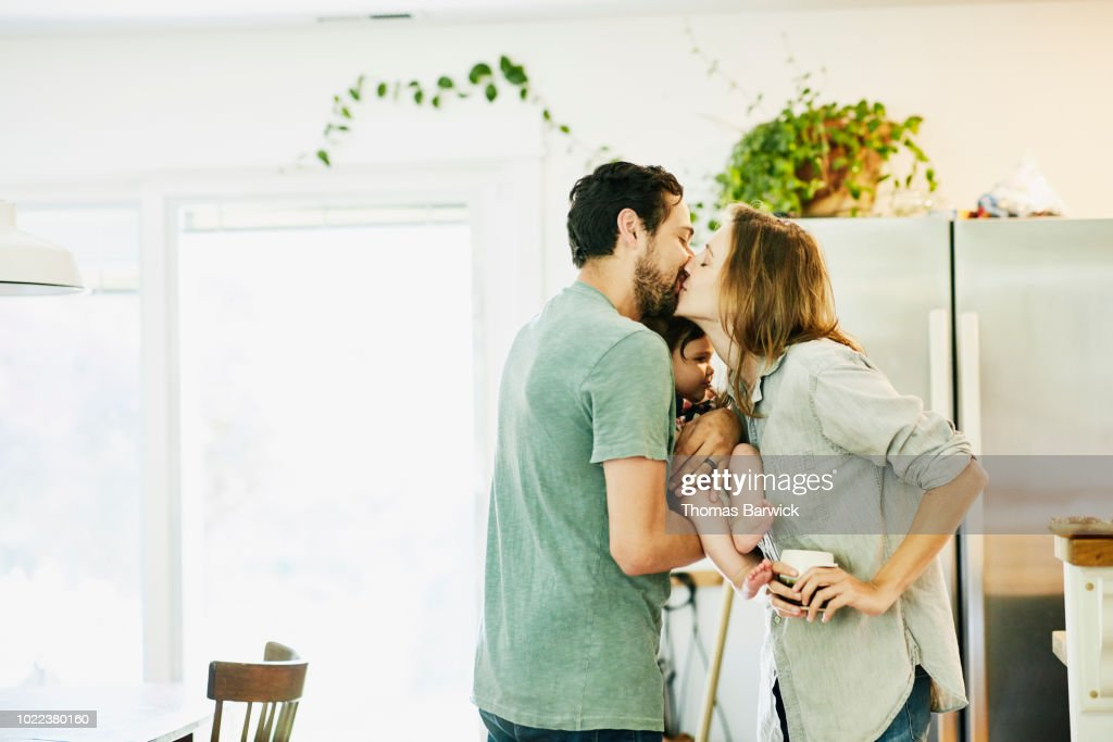 Mother and father kissing while holding infant daughter in kitchen : Stock Photo