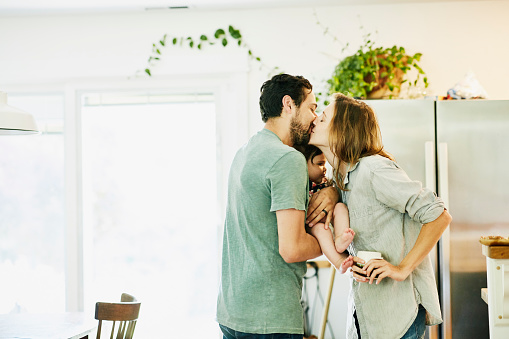 Mother and father kissing while holding infant daughter in kitchen - gettyimageskorea