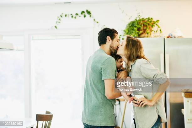 mother and father kissing while holding infant daughter in kitchen - liefde stockfoto's en -beelden