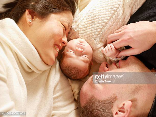 Mother and father lying down with newborn (0-1month)