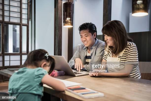 Mère et père sur portable, photo dessin fille