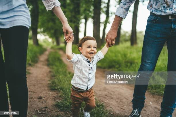 mother and father outdoors teaching baby boy to walk - baby boys stock pictures, royalty-free photos & images