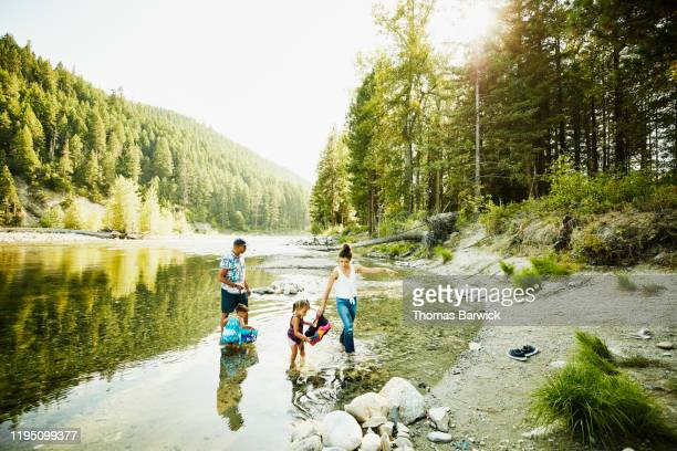 mother and father playing with daughters in river on summer afternoon - nature stock pictures, royalty-free photos & images