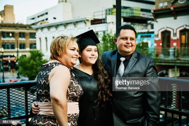 Mother and father posing for picture with graduating daughter during celebration dinner on restaurant deck