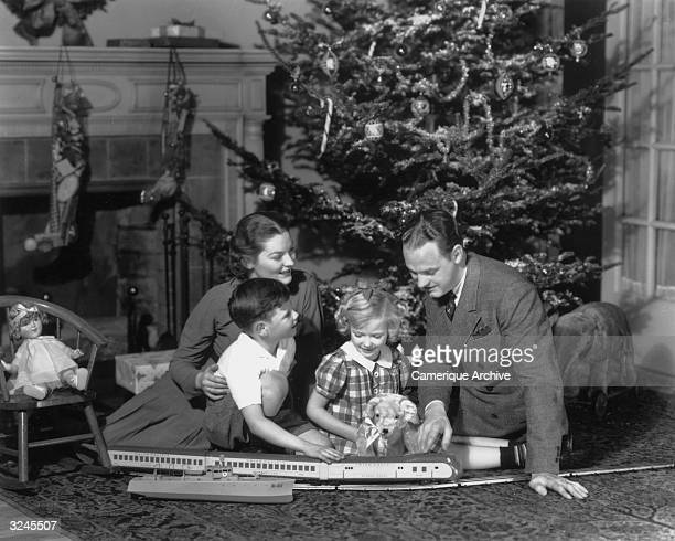 A mother and father sit in front of a Christmas tree with their children playing with their presents a model train set and stuffed toys