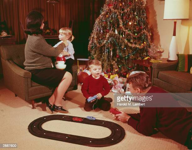 A mother and father sit with their children and a model train set in front of a decorated tree on Christmas circa 1972
